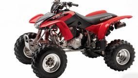 Side Pose Of Honda TRX400EX In Red And White Background